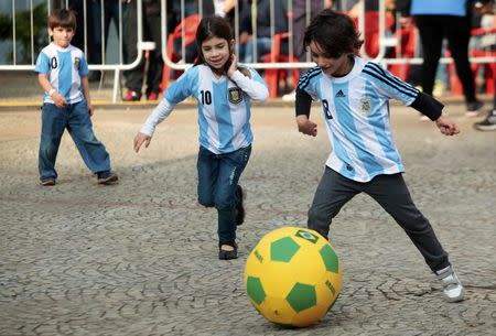 Children wearing Argentina jerseys play soccer at fan gallery in Sao Paulo