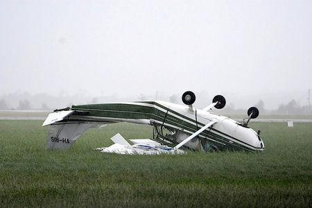 A plane that was flipped by strong winds from Cyclone Debbie is seen at the airport in the town of Bowen. AAP/Sarah Motherwell/via REUTERS