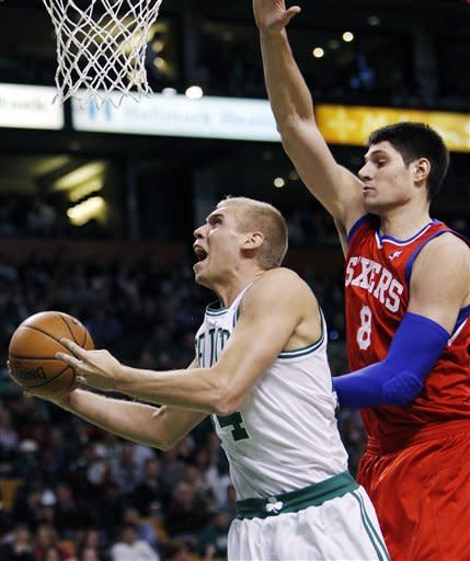 Boston Celtics' Greg Stiemsma, left, shoots in front of Philadelphia 76ers' Nikola Vucevic (8) in the second quarter of an NBA basketball game in Boston, Sunday, April 8, 2012. (AP Photo/Michael Dwyer)