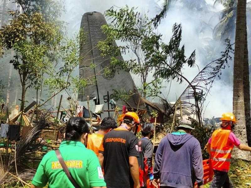Rescuers at the scene where a Philippine military C-130 plane crashed in Patikul town, Jolo province, southern Philippines on Sunday.