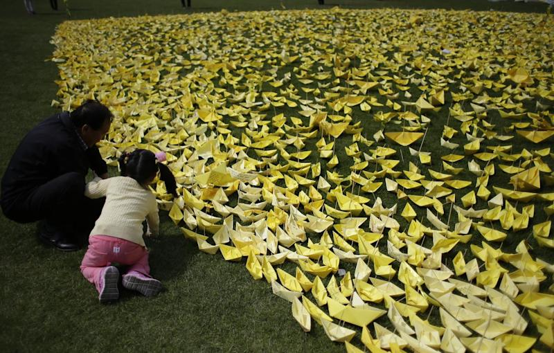A girl with a man puts a paper ship she made to pay tribute to the victims and missing passengers of the sunken ferry Sewol at a group memorial altar in Seoul, South Korea, Wednesday, May 7, 2014. The ferry disaster left more than 200 people dead, with others still missing. Government and civilian divers are fighting rapid currents as they try to retrieve the remaining bodies. (AP Photo/Lee Jin-man)