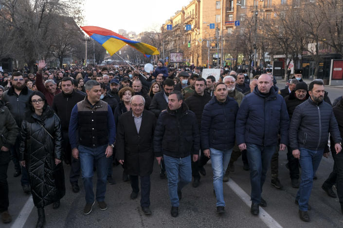 Opposition demonstrators march to the government buildings during a rally to pressure Armenian Prime Minister Nikol Pashinyan to resign in Yerevan, Armenia, Saturday, Feb. 27, 2021. The developments come after months of protests sparked by the nation's defeat in the Nagorno-Karabakh conflict with Azerbaijan. (Hrant Khachatryan/PAN Photo via AP)