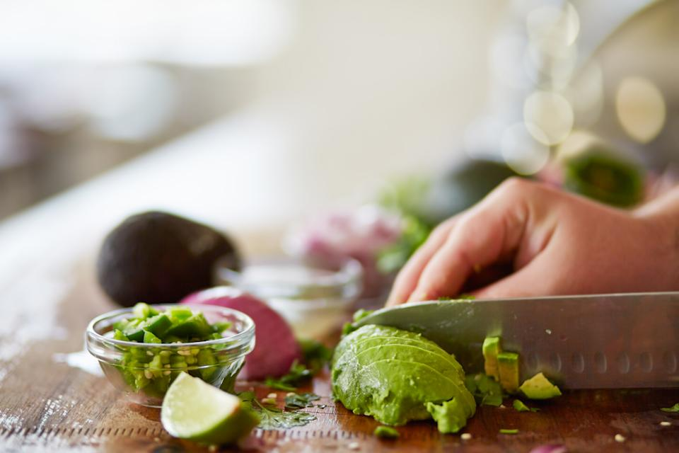 cutting avocado with skin removed and dicing to prepare for guacamole recipe