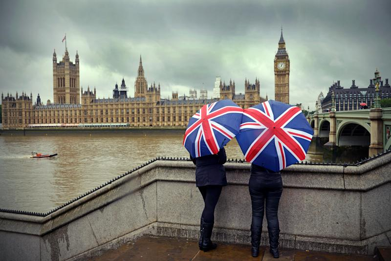"""Tourists huddle beneath British flag umbrellas (they sell them there) during a London summer rainstorm near the Houses of Parliament. A dark cloudy typical summer day!Westminster, LondonUK"""