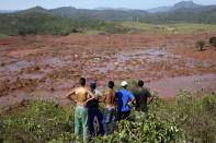 FILE PHOTO: Residents observe the Bento Rodrigues district covered with mud after a dam owned by Vale SA and BHP Billiton Ltd burst in Mariana