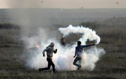 Palestinian protesters throw back a teargas canister fired by Israeli troops during clashes on the Israeli border with Gaza, Saturday, Dec. 9, 2017. - Credit: AP