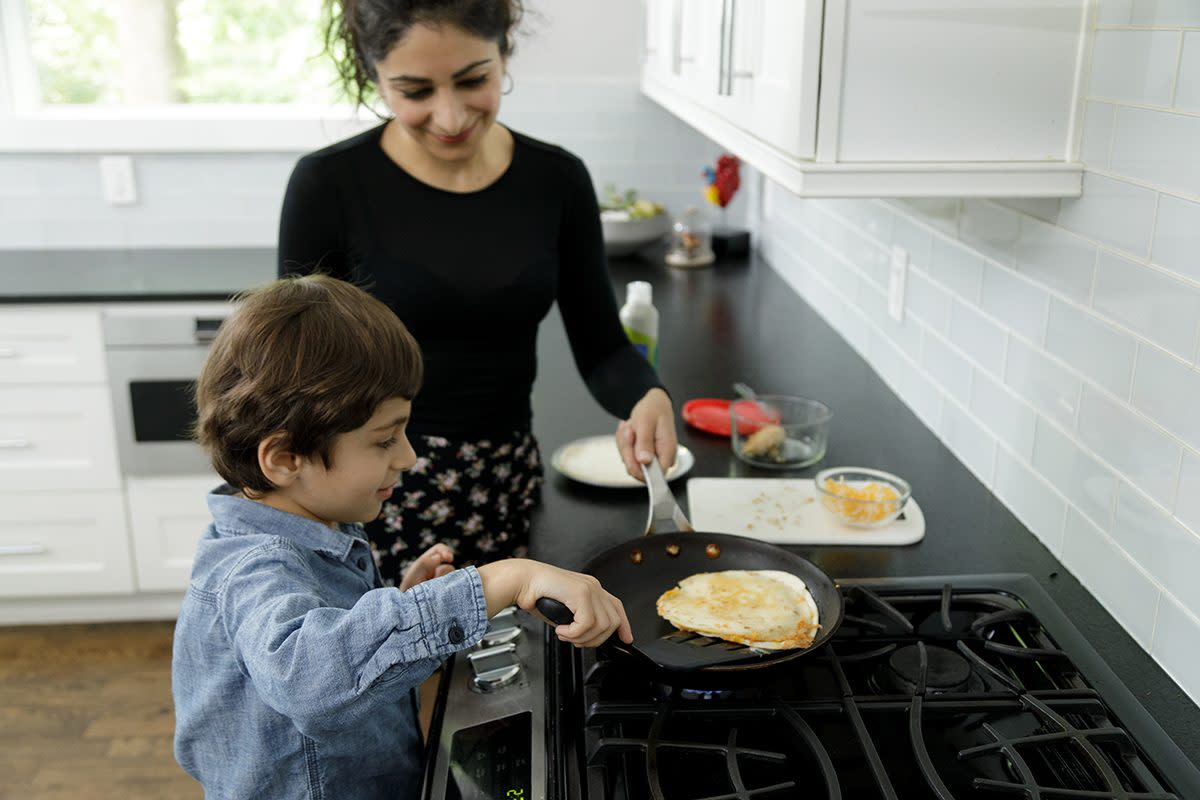 A mother looks on as her son makes a quesadilla. He is flipping it over to cook the other side in the frying pan. He is five years old and is wearing a long sleeved blue shirt, his mother is in a black long sleeved top. Her hair is tied back. They are in a home kitchen with white tiles and white cabinets. They are cooking on a gas range top stove. They are both looking at the food being prepared.