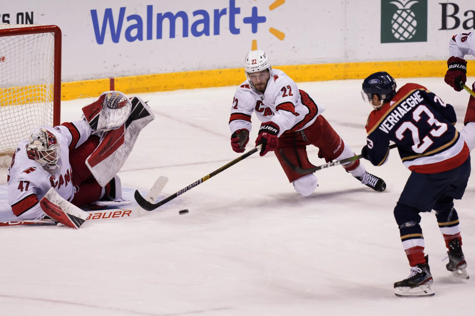 Carolina Hurricanes defenseman Brett Pesce (22) and goaltender James Reimer (47) attempt to defend a shot on goal by Florida Panthers center Carter Verhaeghe (23) during the third period at an NHL hockey game, Saturday, Feb. 27, 2021, in Sunrise, Fla. The Hurricanes defeated the Panthers 4-3. (AP Photo/Marta Lavandier)