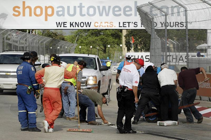 Work crews look over the asphalt patch on the road course during IndyCar's Detroit Grand Prix auto race on Belle Isle in Detroit, Sunday, June 3, 2012. The race was red flagged 63 minutes into the race because of the road condition. (AP Photo/Carlos Osorio)