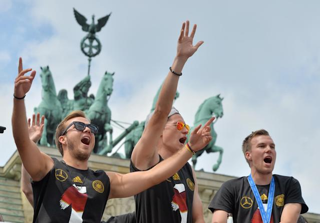 "German soccer players Mario Goetze, left, Julian Draxler ,center, and Kevin Grokreutz celebrate in front of the Brandenburg Gate in Berlin, Tuesday July 15, 2014. Germany's World Cup winners shared their fourth title with hundreds of thousands of fans by parading the trophy through cheering throngs to celebrate at the Brandenburg Gate on Tuesday. An estimated 400,000 people packed the ""fan mile"" in front of the Berlin landmark to welcome home coach Joachim Loew's team and the trophy which returned to Germany for the first time in 24 years. (AP Photo/dpa,Hendrik Schmidt)"