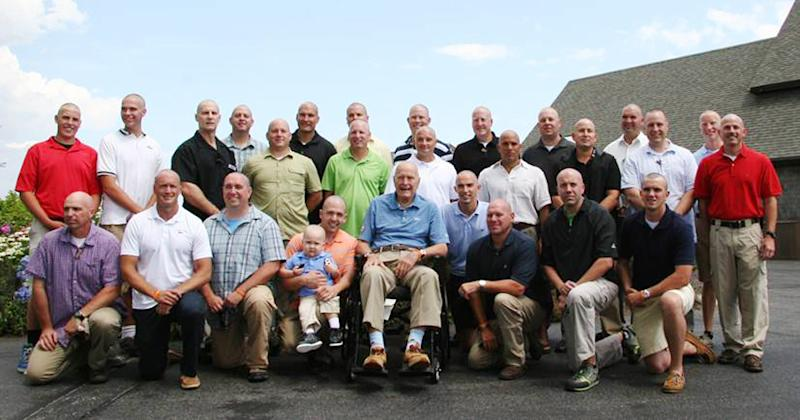 This July 24, 2013 photo provided by the Office of George Bush shows President George H. W. Bush, front center, with his Secret Service security detail including Jon, fifth from left, holding his son Patrick (last name withheld at family's request), 2, in Kennebunkport, Maine. Bush this week joined members of his Secret Service detail in shaving his head to show his support for the two-year-old who is being treated for leukemia and started losing his hair. (AP Photo/Office of George Bush)