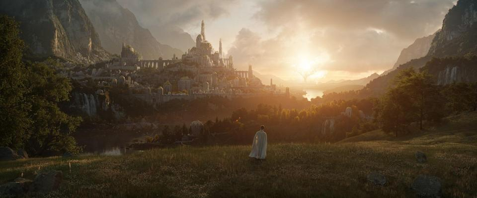 A figure wearing white stands, very small in the image, on a green pasture, facing a massive white kingdom of Middle-earth in The Lord of the Rings Amazon series.