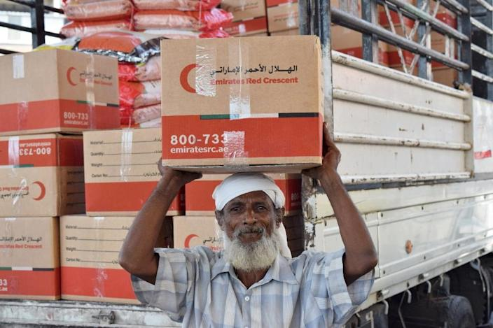 An elderly Yemeni man receives food parcels provided by the Emirati branch of the Red Crescent on October 28, 2015 in the southern port city of Aden (AFP Photo/Saleh al-Obeidi)