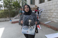 """Sahar Abdullah carries a poster with pictures of the six Palestinian prisoners who escaped from an Israeli jail that says """"the freedom tunnel,"""" during a protest in the West Bank city of Ramallah, Tuesday, Sept. 14, 2021. The cinematic escape of six prisoners who tunneled out of an Israeli penitentiary shone a light on Israel's mass incarceration of Palestinians, one of the many bitter fruits of the conflict. (AP Photo/Nasser Nasser)"""