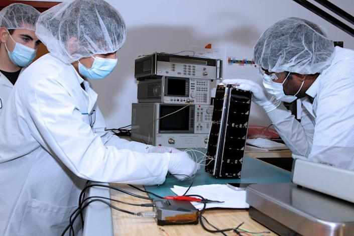 Three people in white lab coats and hairnets working on a satellite roughly the size of a loaf of bread.