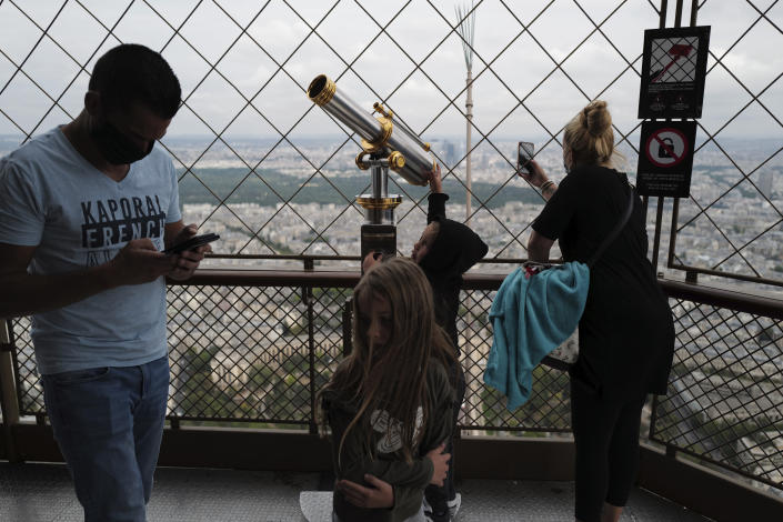 French visitors take photos from the third level during the opening up of the top floor of the Eiffel Tower, Wednesday, July 15, 2020 in Paris. The top floor of Paris' Eiffel Tower reopened today as the 19th century iron monument re-opened its first two floors on June 26 following its longest closure since World War II. (AP Photo/Francois Mori)