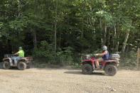 Two all-terrain vehicle riders travel onto an ATV trail, in Gorham, N.H., Friday, July 23, 2021. Rural communities across the country are wrestling with the economic perks and environmental drawbacks of opening up their roads to ATVs. Interest in ATVs has only intensified as more people got outdoors during the pandemic. (AP Photo/Lisa Rathke)