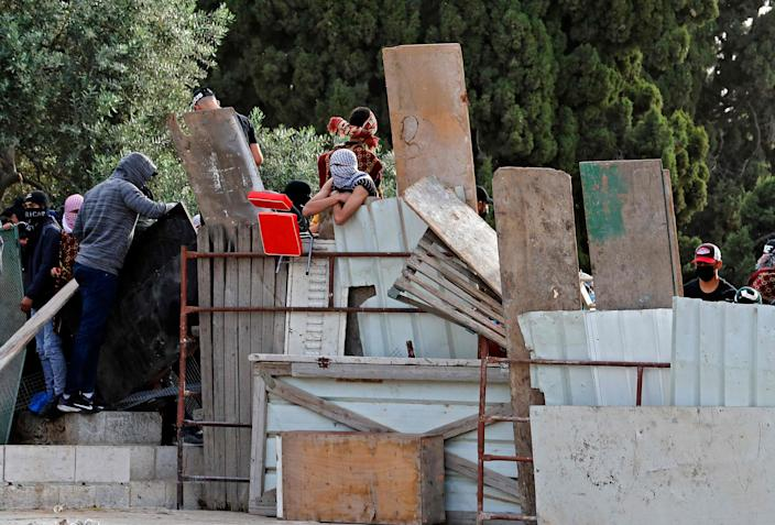 Palestinians erect a barricade at Jerusalem's Al-Aqsa mosque compound on May 10, 2021, ahead of a planned march to commemorate Israel's takeover of Jerusalem in the 1967 Six-Day War.