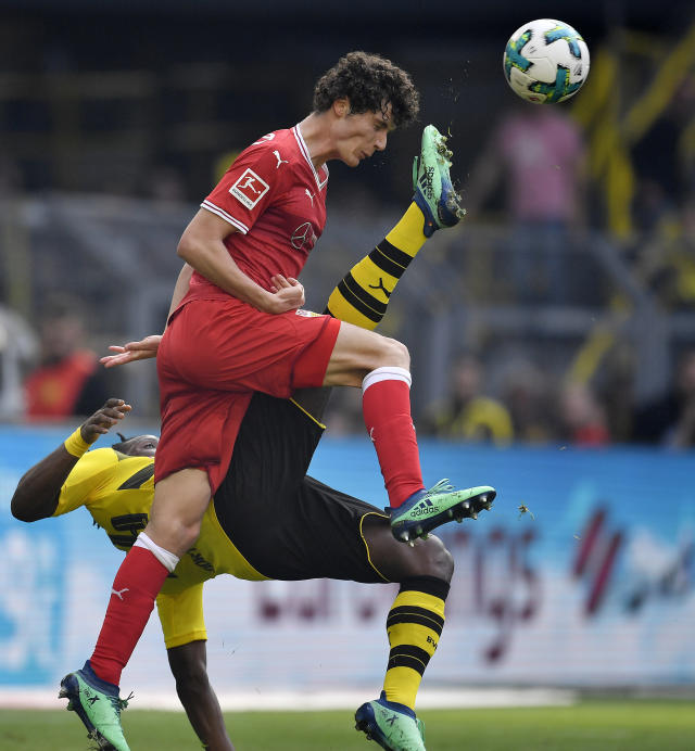 Stuttgart's Benjamin Pavard, up, and Dortmund's Michy Batshuayi challenge for the ball during the German Bundesliga soccer match between Borussia Dortmund and VfB Stuttgart in Dortmund, Germany, Sunday, April 8, 2018. (AP Photo/Martin Meissner)
