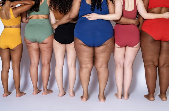 Rear view of group of women with different body type in underwear standing together on white background. Cropped shot of diverse females in lingerie with their arms around each other.