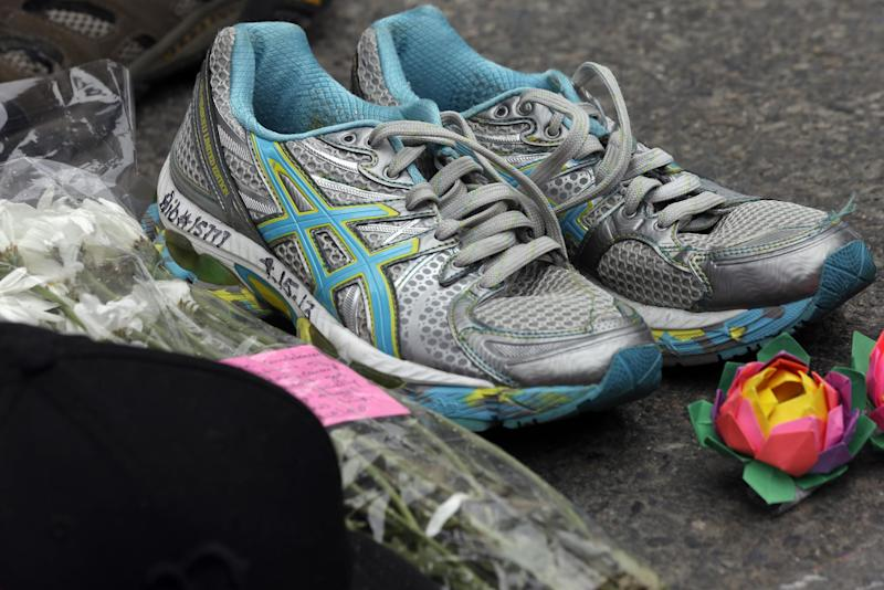 Items are left at a makeshift memorial near the finish line of Monday's Boston Marathon explosions, which killed at least three and injured more than 140, Thursday, April 18, 2013, in Boston. (AP Photo/Matt Rourke)