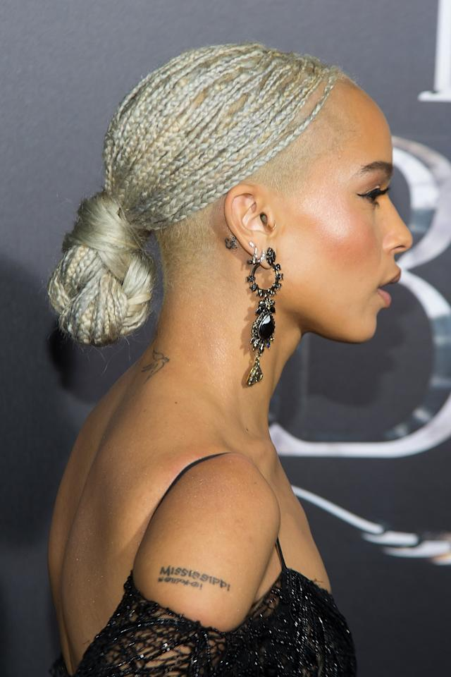 <p>What a look. Kravitz wears micro-sized tree braids that take forever to do but are absolutely worth the wait. She's wearing braiding hair in color 613 (platinum blonde) in a low chignon.</p>