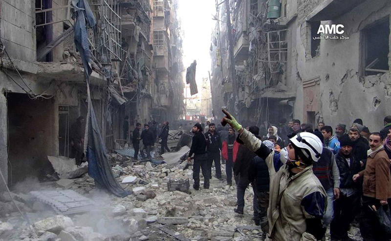 In this Sunday, Dec. 15, 2013 citizen journalism image provided by Aleppo Media Center AMC, which has been authenticated based on its contents and other AP reporting, Syrians inspect damages buildings following a Syrian government airstrike in Aleppo, Syria. The Britain based Syrian Observatory for Human Rights said Monday that dozens of children were among the scores killed in airstrikes on several opposition areas a day earlier. (AP Photo/Aleppo Media Center, AMC)