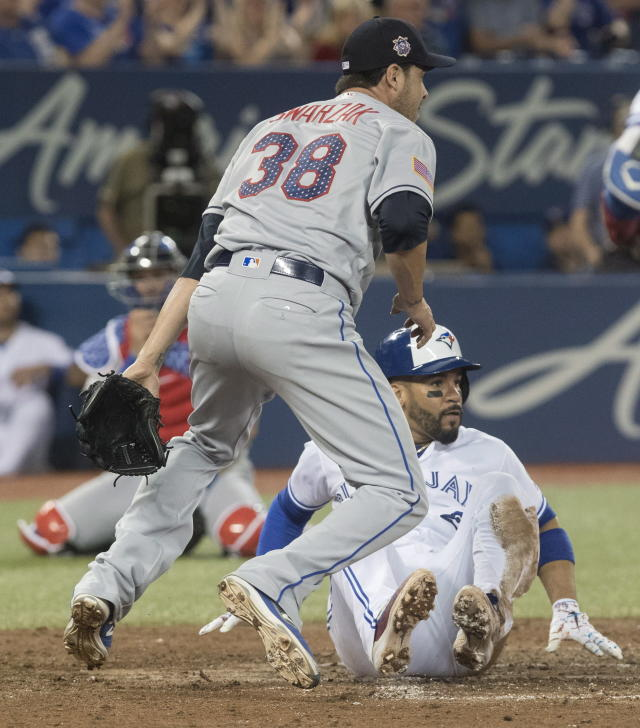 Toronto Blue Jays' Devon Travis scores on a wild pitch by New York Mets pitcher Anthony Swarzak (38) during the seventh inning of a baseball game Tuesday, July 3, 2018, in Toronto. (Fred Thornhill/The Canadian Press via AP)