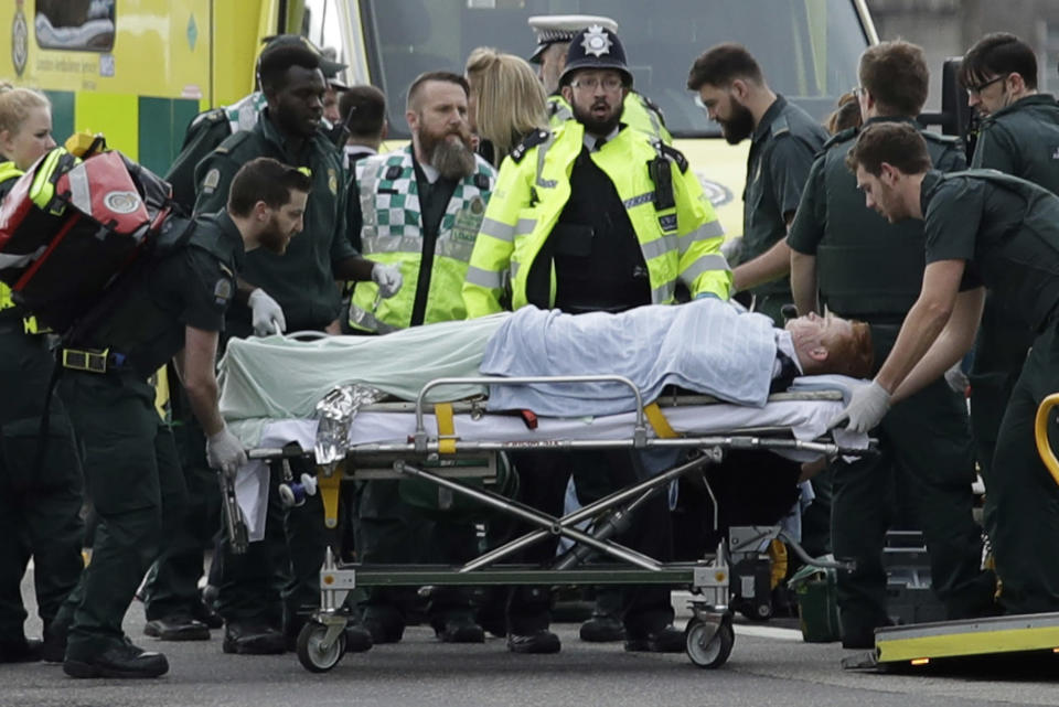 FILE - In this Wednesday, March 22, 2017 file photo emergency services staff provide medical attention to injured people on Westminster Bridge, near the Houses of Parliament in London. In the 20 years since the Sept. 11, 2001 terrorist attacks in the United States, a mixture of homegrown extremists, geography and weaknesses in counterterrorism strategies have combined to turn Europe into a prime target for jihadists bent on hurting the West. (AP Photo/Matt Dunham, File)