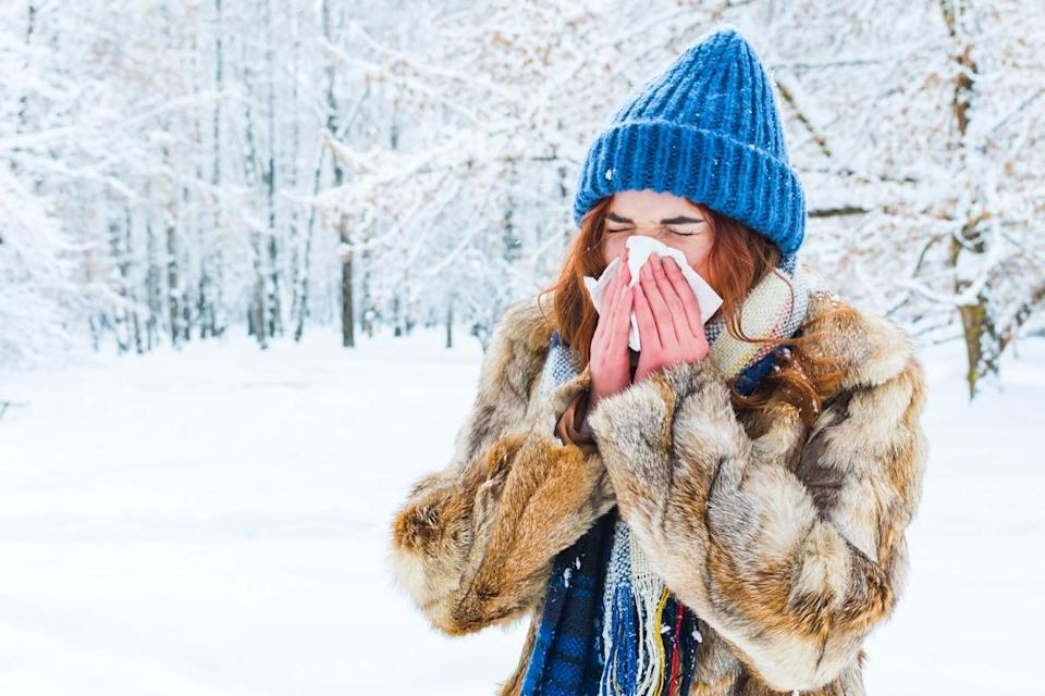 woman in the winter forest. a beautiful girl sneezes into a napkin