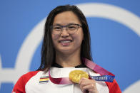 Margaret MacNeil of Canada celebrates on the podium after winning the women's 100-meter butterfly final at the 2020 Summer Olympics, Monday, July 26, 2021, in Tokyo, Japan. (AP Photo/Matthias Schrader)