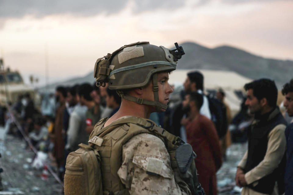 In this image provided by the U.S. Marines, a Marine assigned to Special Purpose Marine Air Ground Task Force-Crisis Response-Central Command assists evacuees during an evacuation at Hamid Karzai International Airport in Kabul, Afghanistan, Friday, Aug. 20, 2021. (Sgt. Isaiah Campbell/U.S. Marine Corps via AP)