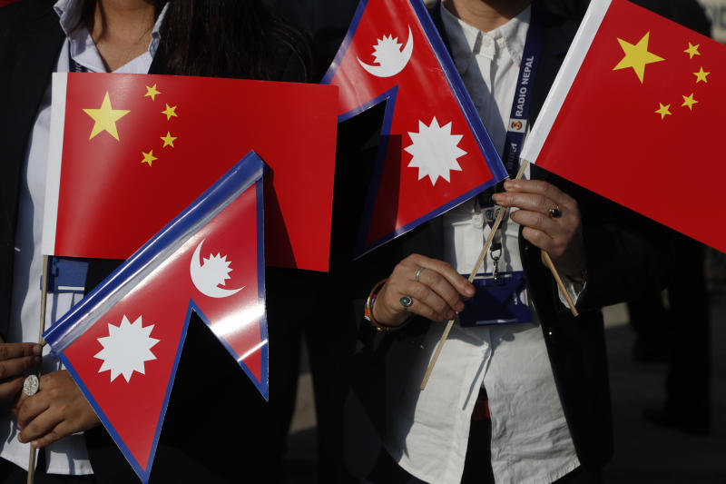 Government officers hold Chinese and Nepalese flag as they wait to welcome Chinese president Xi Jinping  in Kathmandu, Nepal, Saturday, Oct 12, 2019. Xi has become the first Chinese president in more than two decades to visit Nepal, where he's expected to sign agreements on major infrastructure projects. (AP Photo/Niranjan Shrestha)