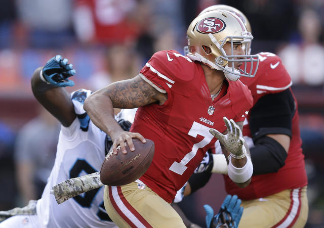 San Francisco 49ers quarterback Colin Kaepernick (7) scrambles away from the rush of Carolina Panthers defensive end Charles Johnson during the third quarter of an NFL football game in San Francisco, Sunday, Nov. 10, 2013. (AP Photo/Ben Margot)