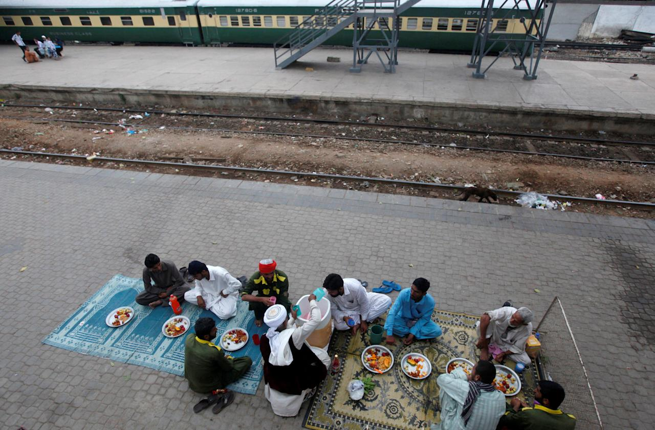 Men sit before breaking their fast during the Muslim holy month of Ramadan, along a platform at Cantonment Railway Station in Karachi, Pakistan, June 22, 2017. REUTERS/Akhtar Soomro