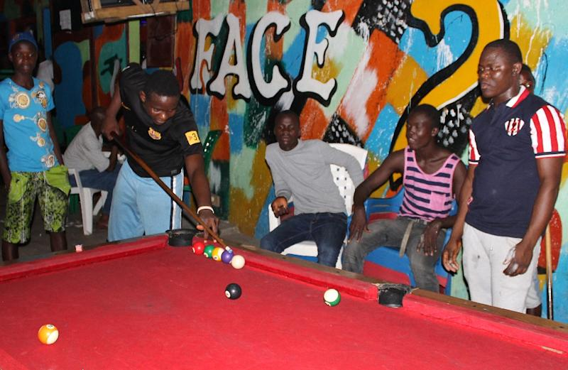 People play pool in Monrovia on February 22, 2015, enjoying their first night of freedom since an Ebola curfew was lifted (AFP Photo/Zoom Dosso)