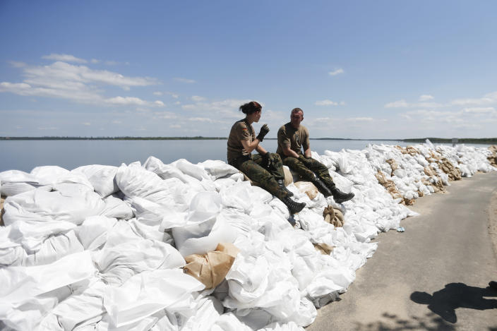 A German soldiers rest during a break on the top of a sand bag wal at Lake Goitzschesee, in Bitterfeld, Saxony-Anhalt Germany, Thursday, June 6, 2013. Heavy reainfalls caused flooding in parts of Germany, Austria and Czech Republic. (AP Photo/Markus Schreiber)