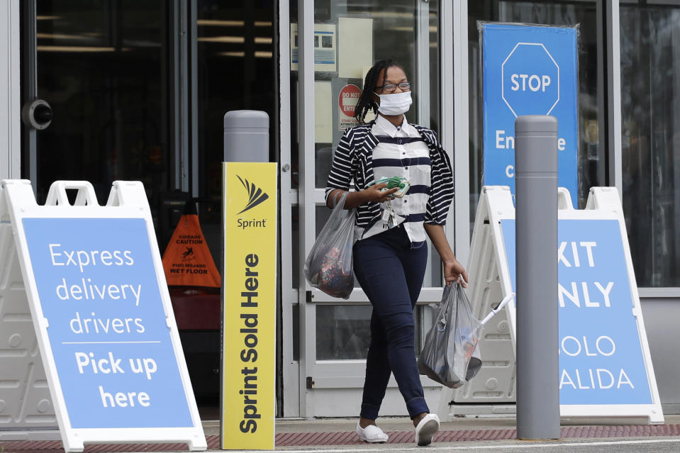 A shopper wears face masks as she leaves a Walmart retail store in Vernon Hills, Ill., Thursday, July 30, 2020. Many retail stores are requiring customers to wear face masks inside all of their stores where local governments do not require it amid the coronavirus pandemic. However, limited enforcement, at Walmart avoids physical confrontations with customers who refuse to wear a mask. (AP Photo/Nam Y. Huh)