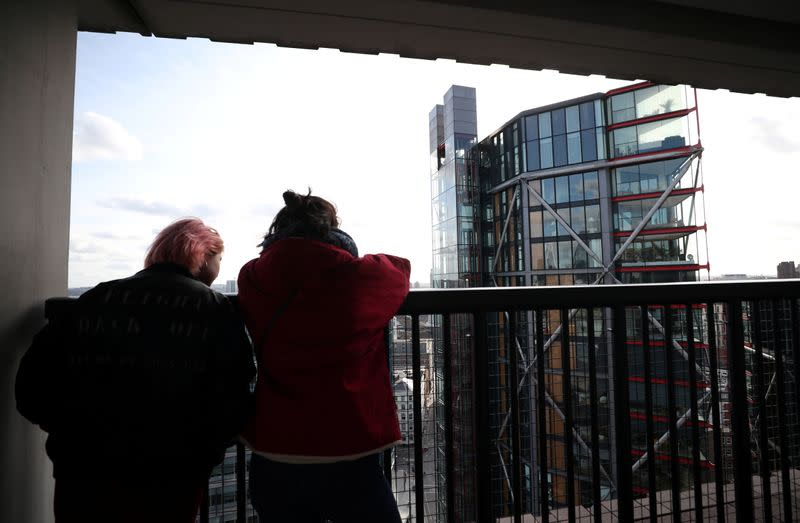 Visitors look out from the Viewing Level towards a luxury block of flats from the Tate Modern gallery in London