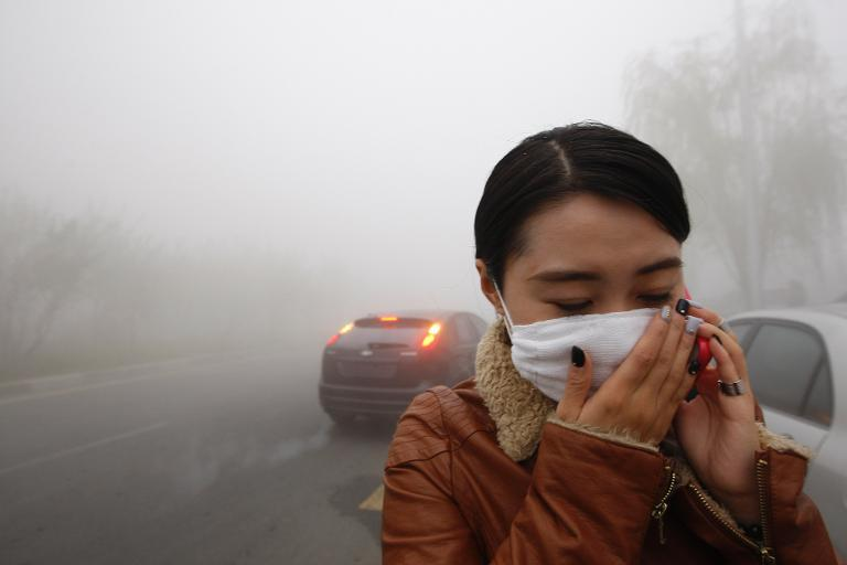 A woman wearing a mask covers her mouth with her hands as she walks in the smog in Harbin, China's Heilongjiang province, on October 21, 2013