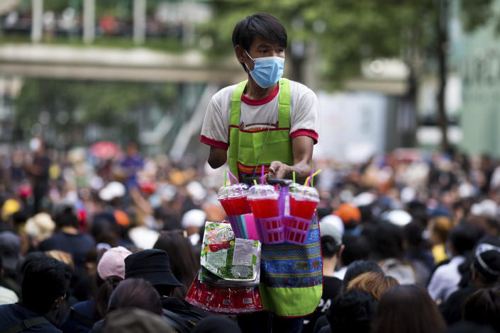 A vendor sells drinks at an anti-government rally at a major intersection in Bangkok, Thailand, Wednesday, Nov. 18, 2020. Police in Thailand's capital braced for possible trouble Wednesday, a day after a protest outside Parliament by pro-democracy demonstrators was marred by violence that left dozens of people injured. (AP Photo/Wason Wanichakorn)