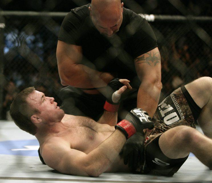 Referee Dan Miragliotta tends to Matt Hughes after Hughes was knocked out in 21 seconds by B.J. Penn at UFC 123 on Sept. 20, 2010. (The Associated Press)