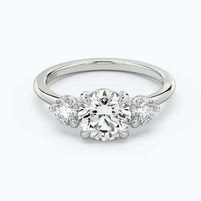 "$1305, Vrai. <a href=""https://www.vrai.com/engagement-rings/three-stone/round-brilliant/white-gold"" rel=""nofollow noopener"" target=""_blank"" data-ylk=""slk:Get it now!"" class=""link rapid-noclick-resp"">Get it now!</a>"