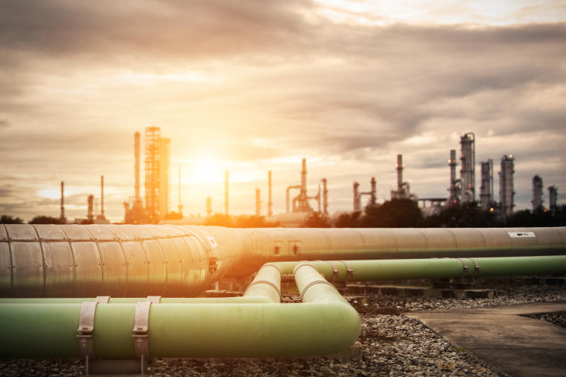 Pipelines heading into an industrial complex with the sun shining in the background.