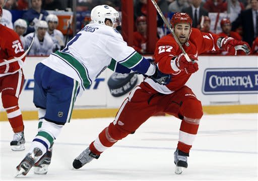 Detroit Red Wings defenseman Kyle Quincey is checked by Vancouver Canucks defenseman Dan Hamhuis (2) in the first period of an NHL hockey game in Detroit, Thursday, Feb. 23, 2012. (AP Photo/Paul Sancya)