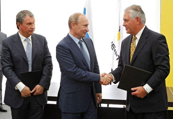 Russian President Vladimir Putin, center, and Exxon Mobil Corp. CEO Rex Tillerson shake hands on June 15, 2012.