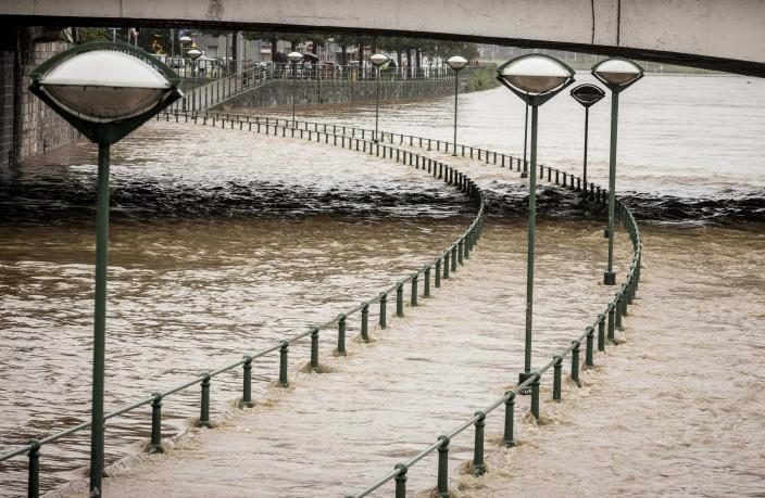Light posts along a pathway of the Meuse river as it rises during flooding in Liege, Belgium, Thursday, July 15, 2021. Heavy rainfall is causing flooding in several provinces in Belgium with rain expected to last until Friday. (AP Photo/Valentin Bianchi)