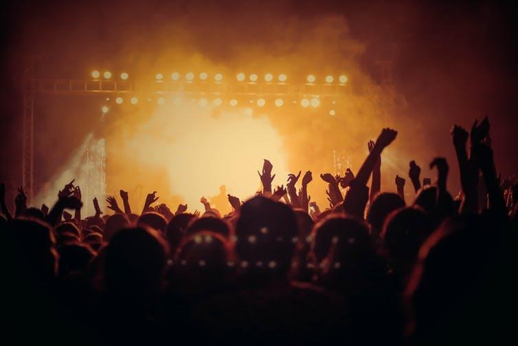 People at a concert with arms up and smoke-filled room.