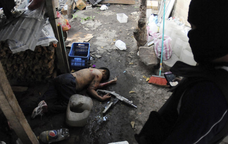 In this April 7, 2013 photo, a hooded policeman stands over the body of a man who was killed during a shootout with police who were carrying out an offensive against gang members in Tegucigalpa, Honduras. The officers had surrounded the house where two gangsters had holed up after a chase with police. At least five times in the last few months, members of a Honduras street gang were killed or went missing just after run-ins with the national police, The Associated Press has determined, feeding accusations that they were victims of federal death squads. (AP Photo/Fernando Antonio)