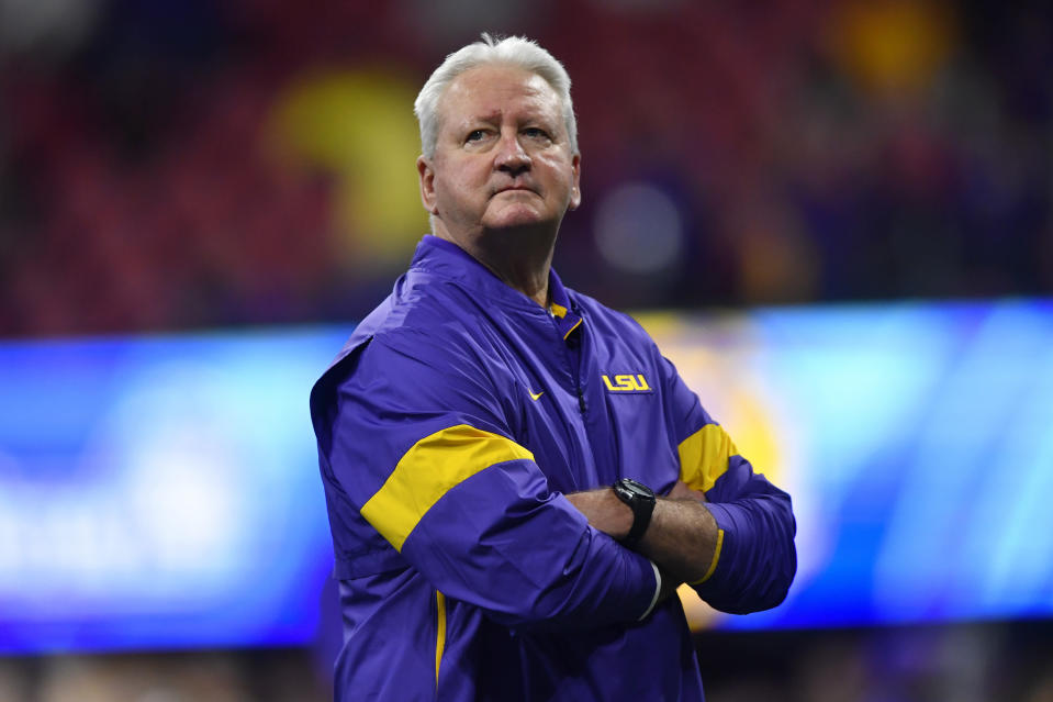 LSU Offensive Coordinator Steve Ensminger watches teams warm up before the first half of the Peach Bowl NCAA semifinal college football playoff game between LSU and Oklahoma, Saturday, Dec. 28, 2019, in Atlanta. Ensminger's daughter-in-law, Carley McCord, died in a plane crash Saturday in Louisiana on the way to the game. (AP Photo/John Amis)